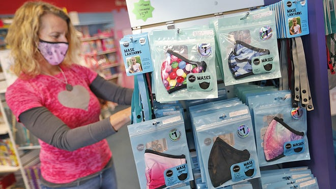 Shop owner Julie Ritchie loads top selling masks on a sales rack.  Back to school mask shopping at The Toy Box in Hanover on Wednesday September 16, 2020  Greg Derr/ The Patriot Ledger