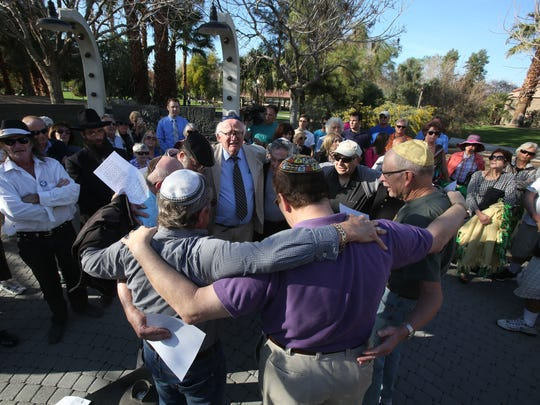 Members of the Jewish community embrace for a prayer during the Holocaust Remembrance Observance at Palm Desert's Civic Center Park. Tuesday's observance also marked the 70th anniversary of the liberation of the Auschwitz concentration camp.