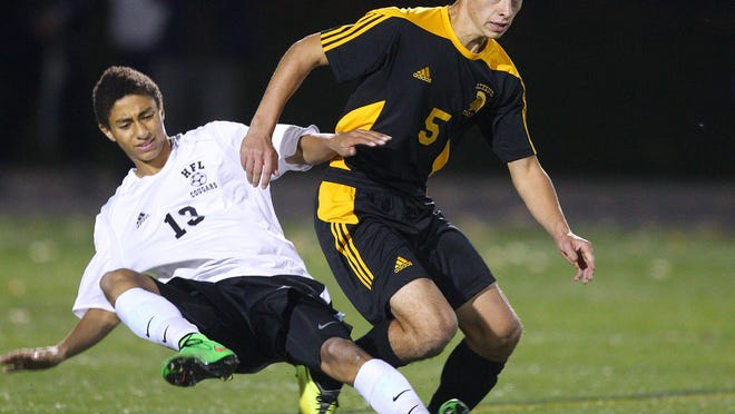 Greece Athena's Omero Paris (5) tackles Honeoye Falls-Lima's Hunter Burri (13) near midfield during the Trojans' 3-1 Class A state tournament qualifier victory Tuesday. The Cougars took an early 1-0 lead before Athena scored three unanswered goals.