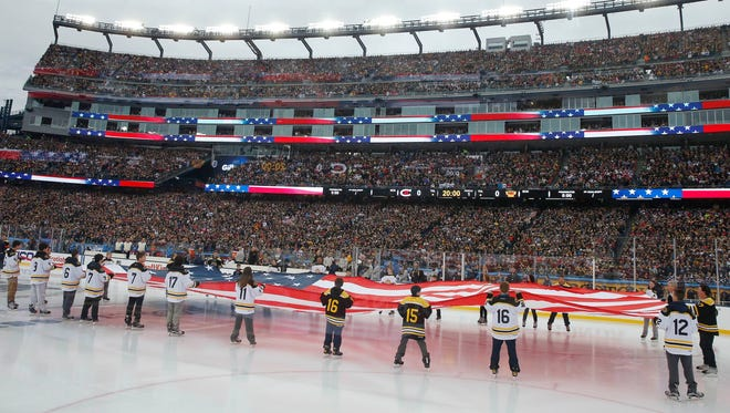 Young skaters hold an American flag during the playing of the national anthem before the NHL Winter Classic hockey game between the Boston Bruins and the Montreal Canadiens at Gillette Stadium in Foxborough, Mass.