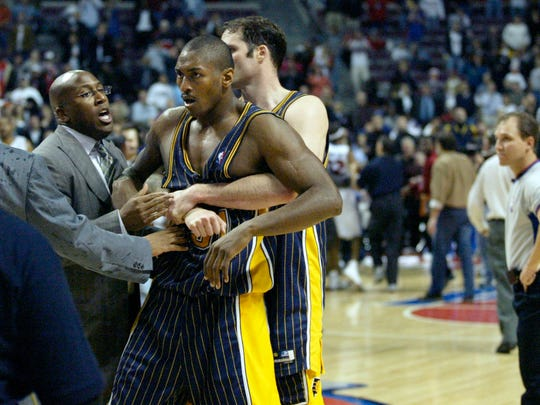 Indiana Pacers' Ron Artest is restrained by Austin Croshere before being escorted off the court following their fight with the Detroit Pistons and fans Friday, Nov. 19, 2004, in Auburn Hills, Mich. NBA commissioner David Stern suspended Artest for the remainder of this season, Sunday Nov. 21, 2004, and disciplined eight other members of the Pacers and Pistons, sending a strong message that the league won't tolerate the type of unprecedented violence displayed Friday night.  (AP Photo/Duane Burleson)