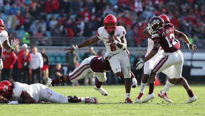Louisville's Lamar Jackson breaks a tackle during second half action against Mississippi State in the TaxSlayer Bowl. Dec. 30, 2017.