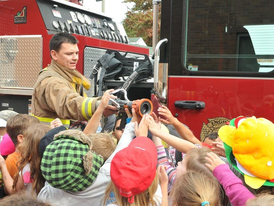 """Port Clinton firefighter Jason Adkins shows students a hose from a department fire engine at Bataan Elementary's """"Safety Day"""" on Thursday."""