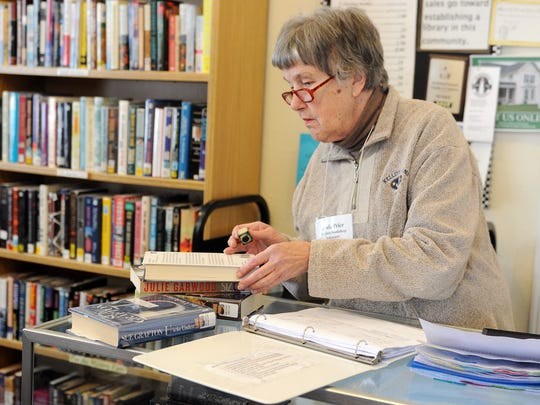 Linda Price, a volunteer at the Ex Libris Bookshop, checks books back in on a Saturday afternoon in 2015. The shop is closing after 14 years in Marblehead.