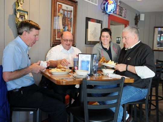 Dick Piro, of Marblehead, David Druspacky, of Marblehead and Skip Muir, of Michigan, smile as Marblehead Galley waitress Cheyanne Dine serves them their lunch on Monday.