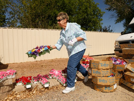 Aztec Senior Center member Norma Briley sorts through flowers Thursday during a beautification project at the Aztec Cemetery.