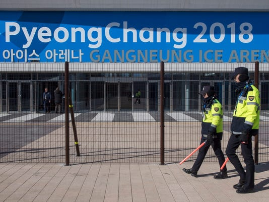 Police officers walk the perimeter of the Gangneung Ice Arena where the figure skating and short track speed skating will be held during the Pyeungchang Winter Olympics Monday, Feb. 5, 2018 in Gangneung, South Korea. (Paul Chiasson/The Canadian Press via AP)