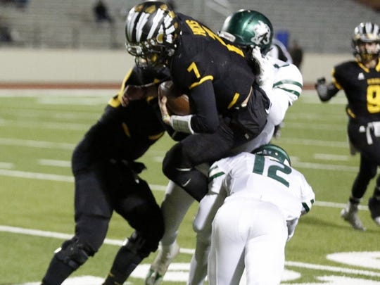 Seminole quarterback Brett Hicks is upended by Iowa Park's Colton Dickerson (12) and Chris Edwards in Friday's Region I-4A area playoff game at Peoples Bank Stadium in Wolfforth.