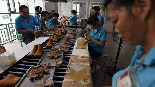 This photo taken on September 14, 2016 shows workers on a production line at the Huajian shoe factory, where about 100,000 pairs of Ivanka Trump-branded shoes have been made over the years amongst other brands, in Dongguan, in south China's Guangdong province. At the Dongguan factory, which employs some 15,000 people, it takes more than 200 workers to move a single pair of shoes from the concept stage to the loading dock.