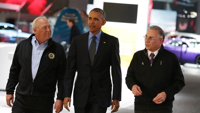President Barack Obama, center, NAIAS Chairman Paul Sabatini, right, and UAW President Dennis Williams visit the 2016 North American International Auto Show at Cobo Center downtown Detroit on Jan. 20, 2016.