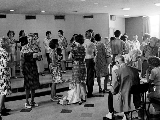 Nashville Then: August 1974: A toddler, center, contemplates the hemline vote in polling lines at Commerce Union Bank in Green Hills during the elections on Aug. 1, 1974.