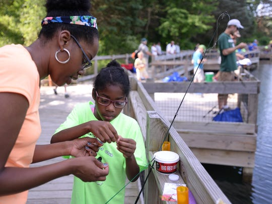 Holt resident Tylene Walker helps her daughter Jade, 8, with a lure at Burchfield County Park in Holt on Saturday, June 11, 2016, during Youth Sports Day.