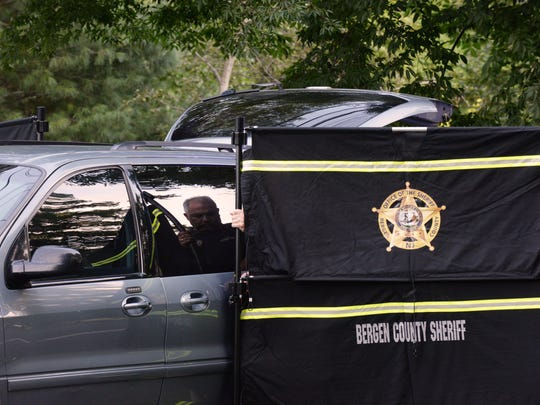 A body was found at 600-660 Kinderkamack Road in Oradell on Thursday August 24, 2017. Bergen County Sheriff Officers and Oradell Police Officers secure the scene. A reflection of an officer is seen in the medical examiner's van.