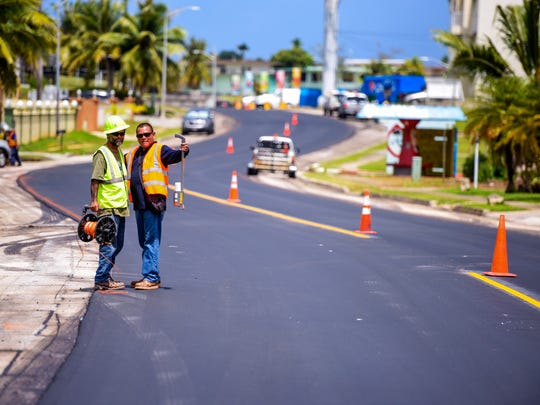Department of Public Works employees coordinate their efforts to restripe the newly paved road surface of Route 24A, also known as Pale Kieran Hickey Drive, on Friday, June 22, 2018. Sinajana Mayor Robert Hofmann says he appreciates the road improvements because the non-skid application raises the safety factor for the residential street and the road serves as an alternate route for traffic, if lanes on Route 4 should become closed or restricted. A length of approximately 2,500 feet of non-skid asphalt was applied to the street the previous day, said Darren Muna, DPW highway maintenance supervisor.