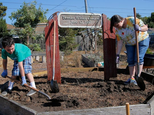Mission Park second-grader Jonah Keltion, and California State University Monterey Bay senior Zareen Kilpatrick work during the Square Foot Gardening program at Mission Park Elementary School in Salinas.