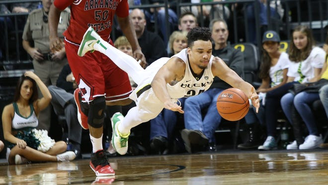 Oregon's Dillon Brooks dives for a loose ball ahead of Arkansas State's Anthony Livingston (50) during the first half of an NCAA college basketball game Wednesday, Nov. 25, 2015, in Eugene.