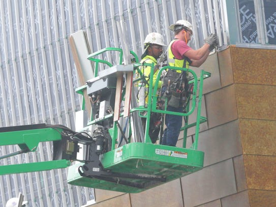 Workers use a lift to install zinc panels on the northwest
