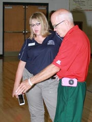 BGM P.E. Instructor Corky Stuart discusses the newly refurbished gym floor at BGM Community Schools with Robin Lilienthal, Provost, Marshalltown Community College.