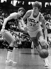 UCLA's Bill Walton dribbles around San Francisco's Eric Fernston in the NCAA west regional playoff in Tucson March 1974.  All-American Walton and his teammates are after their eighth straight national championship.  (AP Photo)