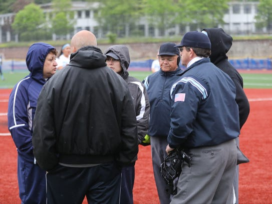 Umpires and coaches talk after the first inning.  After