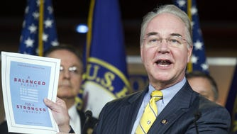 Rep. Tom Price holds up a GOP budget proposal, Washington, March 17, 2015.