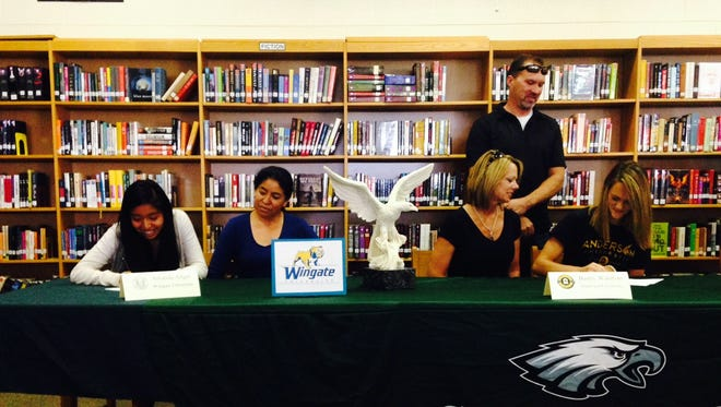 East Henderson's Amanda Angel, left, and Bailey Waldbart have signed with college track programs.