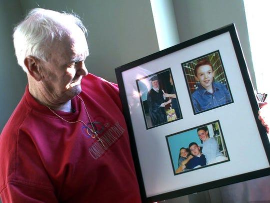 Thomas McGlyn holds photos of his son David that hang