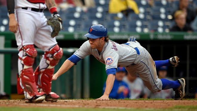 The Mets' Matt den Dekker starts his slide toward home to score on Wilmer Flores' RBI single in the eighth inning Thursday afternoon against Washington. The Mets won 7-4.