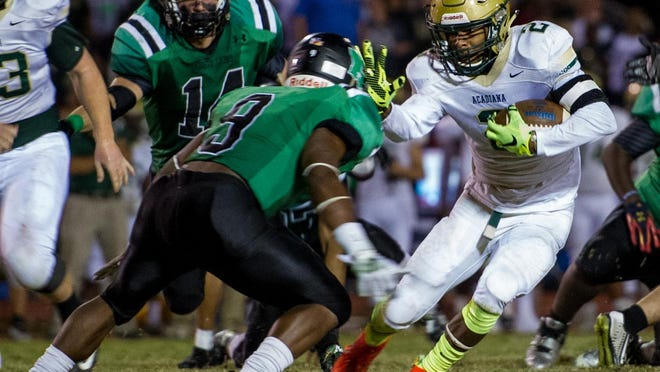 Acadiana running back Jayrin Wilson(2) jukes away from Lafayette cornerback Reid Barfield (8) on Friday night.