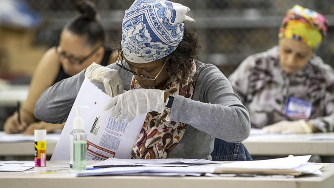 An election worker examines early mail-in ballots at the Supervisor of Elections Service Center in Riviera Beach on March 5.