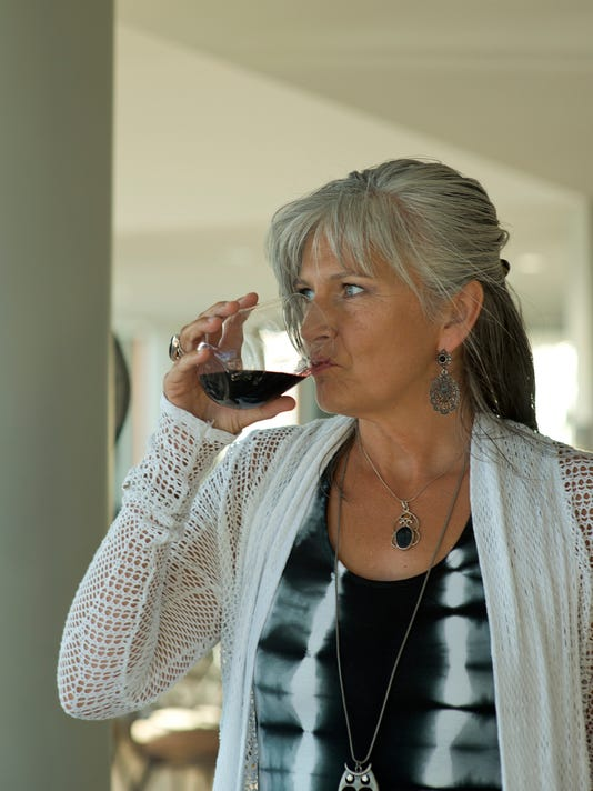 Beautiful mature Woman sipping from Red Wine Glass