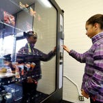 In this Dec. 23, 2013 photo, a 12-year-old girl, who declined to be identified, makes a purchase at a vending machine in Seattle. (AP Photo/Elaine Thompson)