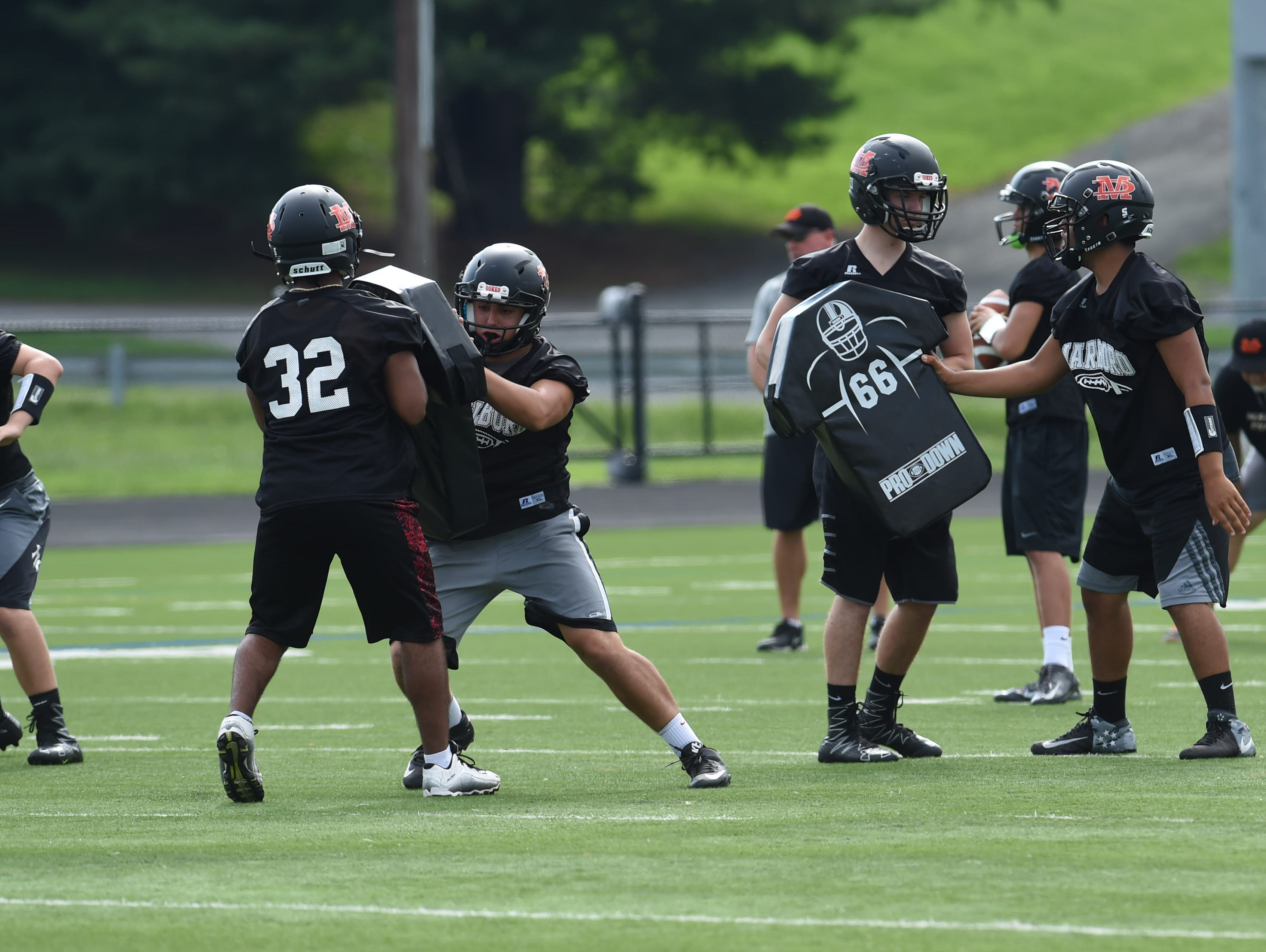 Junior Nico Ramos, left, blocks a teammate during football preseason practice at Marlboro High School.