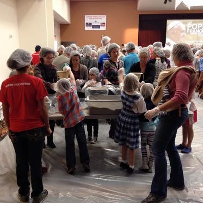 Hundreds of volunteers prepare and pack food bound