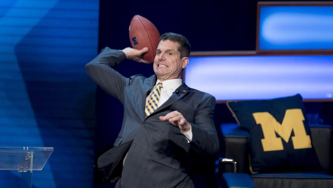 """UM coach Jim Harbaugh plays catch with the crowd at Wednesday's glitzy Signing Day festivities at Ann Arbor's Hill Auditorium. """"I wanted to do something awesome. It was awesome with a capital 'A.'"""""""