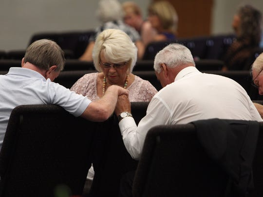 Members of the First United Methodist Church in Punta Gorda pray before the funeral of Mary Knowlton.