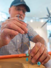 Kirk Marshall builds a wire sculpture during the SUMA Birthday Bash at the Southern Utah Museum of Art Saturday, July 7, 2018. Guests participated in crafts and games at the party.