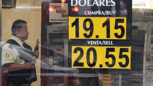 A guard stands inside a bank next to a sign displaying the exchange rate of the U.S dollar in Mexico City, Wednesday, Nov. 9, 2016.