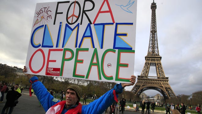 An activist hold a poster during a demonstration Dec. 12 near the Eiffel Tower, in Paris during the COP21, the United Nations Climate Change Conference.