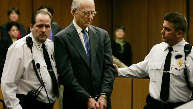 In this 2005 file photo defrocked priest Paul Shanley is led from Middlesex Superior Court in Cambridge, Mass. in handcuffs following his sentence of 12 to 15 years in prison for raping a boy repeatedly in the 1980s.