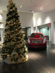 A red Cadillac SRX sits ready for Santa in the Courtesy