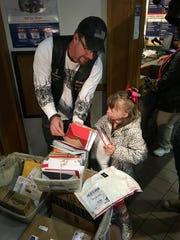 Safyre Terry, 8, and Kevin Clark collect cards and