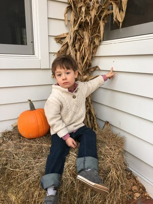 Daniel Wochinske, 3, points to the bullet hole in his family's house in New Denmark.