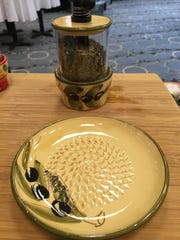 This grater is a small, ceramic plate with bumps in the bottom. It grates the garlic when you rub it over the bumps. It comes with a small brush so you can sweep the finely minced garlic into whatever you're cooking.