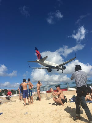 Planes land close to the beach at Maho Beach in St. Maarten.
