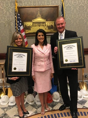 Lee Ann and Allen Johnston pose with Gov. Nikki Haley, holding the Order of the Palmetto award they recently received.