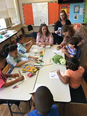 Children work on a coloring project at the Summer Skills Workshop for students with autism and related disorders on Tuesday, June 21, 2016.