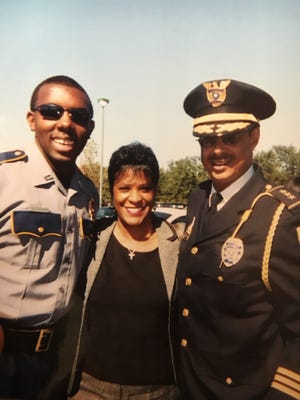 In this undated photo provided by Trenisha Jackson, her husband, Baton Rouge Police Officer Montrell Jackson, from left, his aunt Darlene Cavalier and former Baton Rouge Police Chief Jeff LeDuff pose for a photo at a graduation ceremony to become a police officer in Baton Rouge, La. Montrell Jackson and two other Baton Rouge law enforcement officers investigating a report of a man with an assault rifle were killed Sunday, July 17, 2016, less than two weeks after a black man was fatally shot by police here in a confrontation that sparked nightly protests that reverberated nationwide.