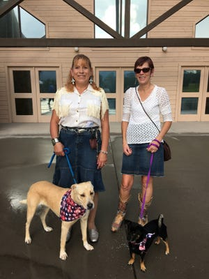 Humane Society volunteers Susan Hoffer (left) and Lynda Remus, and shelter residents Dolly (left) and Panchito were part of the reception committee at the Furr Ball.