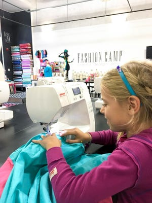 A young sewer goes through the steps of designing, measuring and sewing her own creation at Fashion Camp - Create. Design. Sew. in Tuscon, Calif.